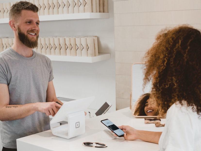 レジを打つ男性従業員と談笑するスマートフォンを持った女性客